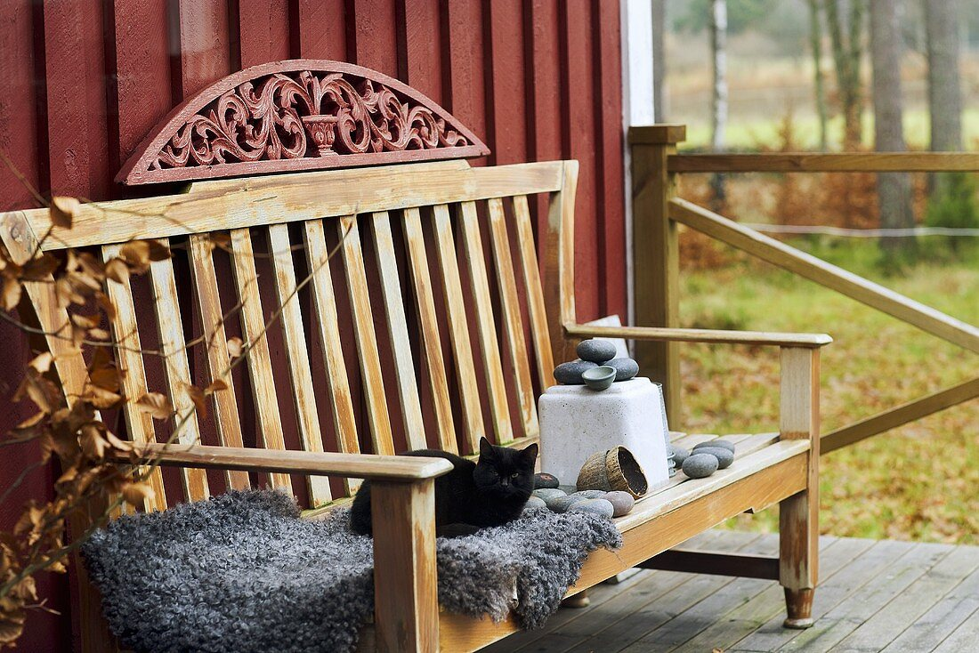 A comfortable terrace with a cat on a fluffy blanket on a wooden bench in front of a red wooden facade