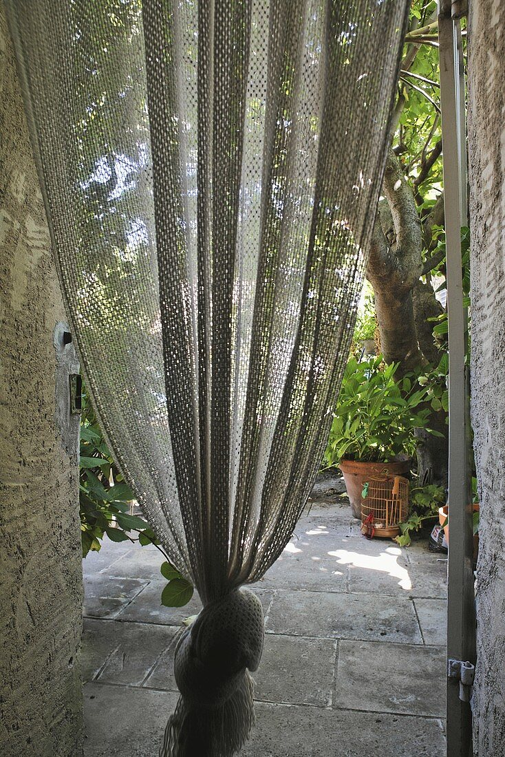 Curtain tied in a knot with a view of a stone terrace