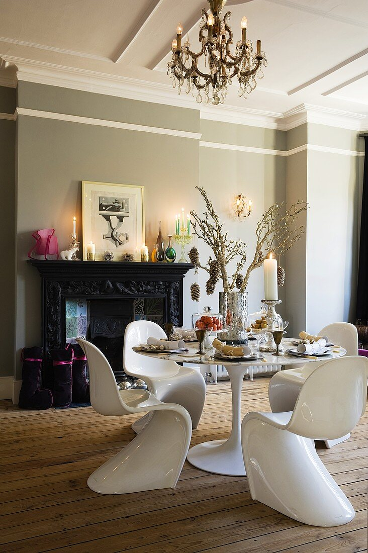 An elegant dining room with Bauhaus-style white plastic chairs and a table in front of a fireplace