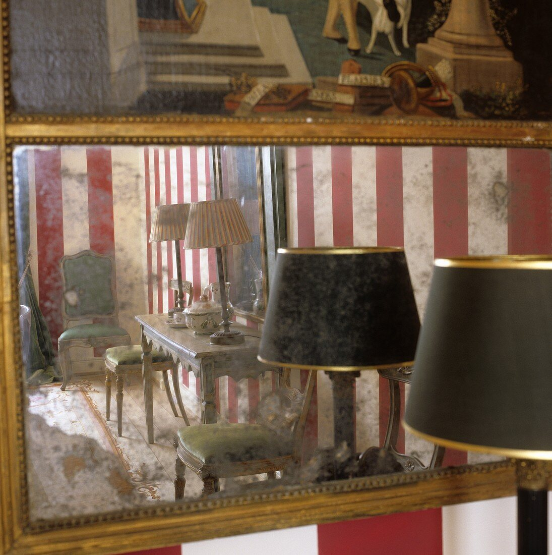 A table lamp with a black shade in front of an antique wall mirror