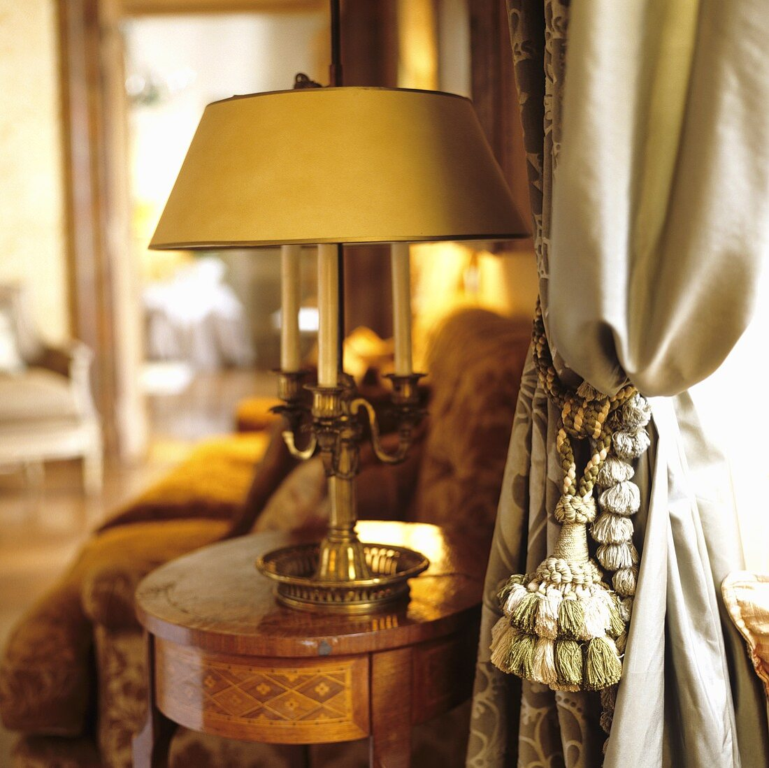 An antique table lamp on a Baroque table and a curtain with a cord tie