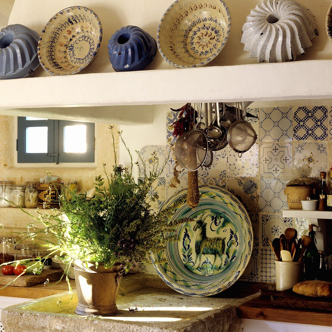 A pot of herbs on a stone shelf and antique cake tins on the mantelpiece