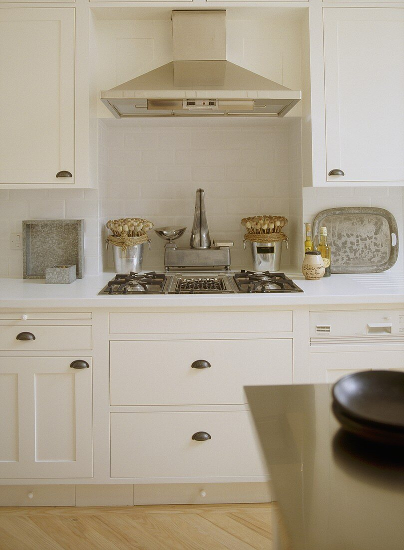 A detail of a modern, country kitchen with painted units, stainless steel gas hob, extractor fan