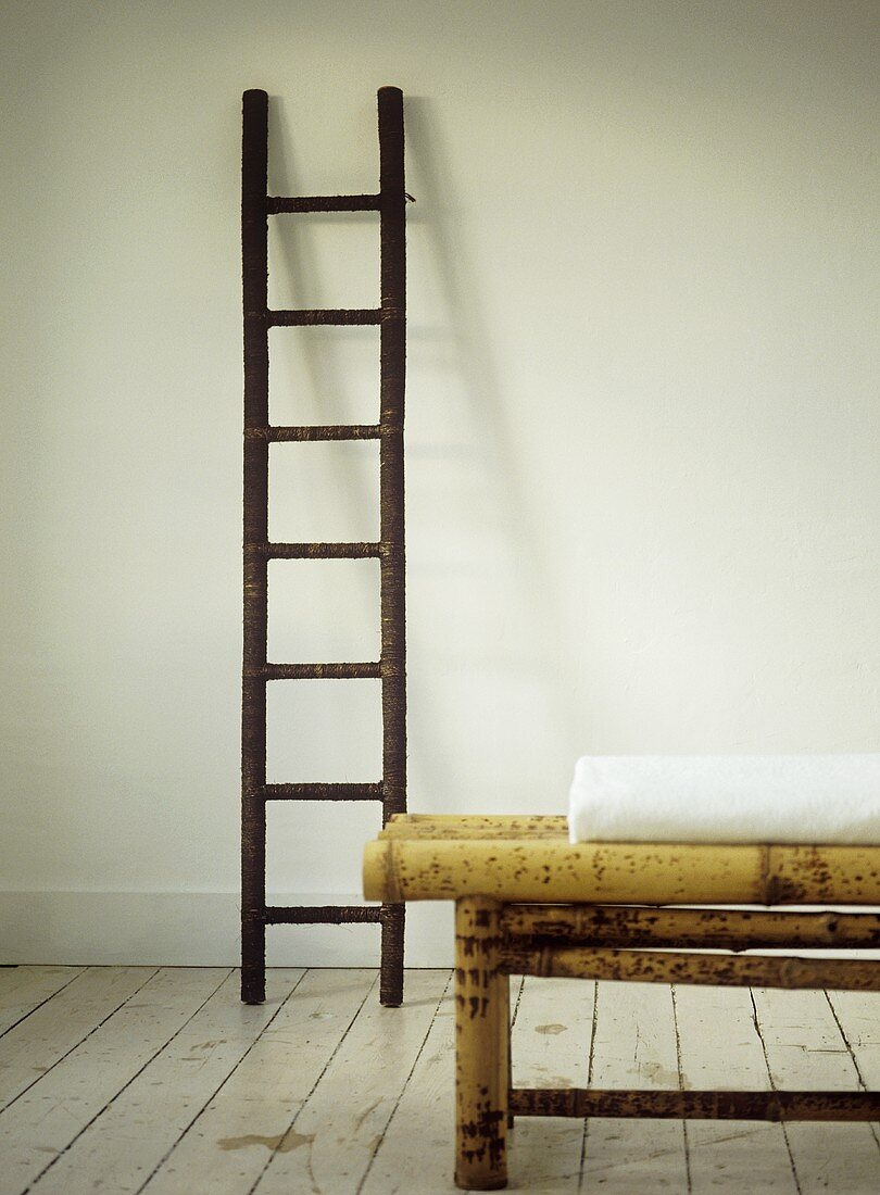 Folded white blanket on bamboo coffee table with  ladder in background