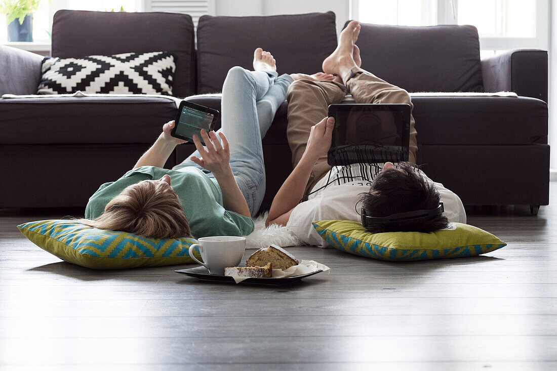 Caucasian couple using digital tablets on floor