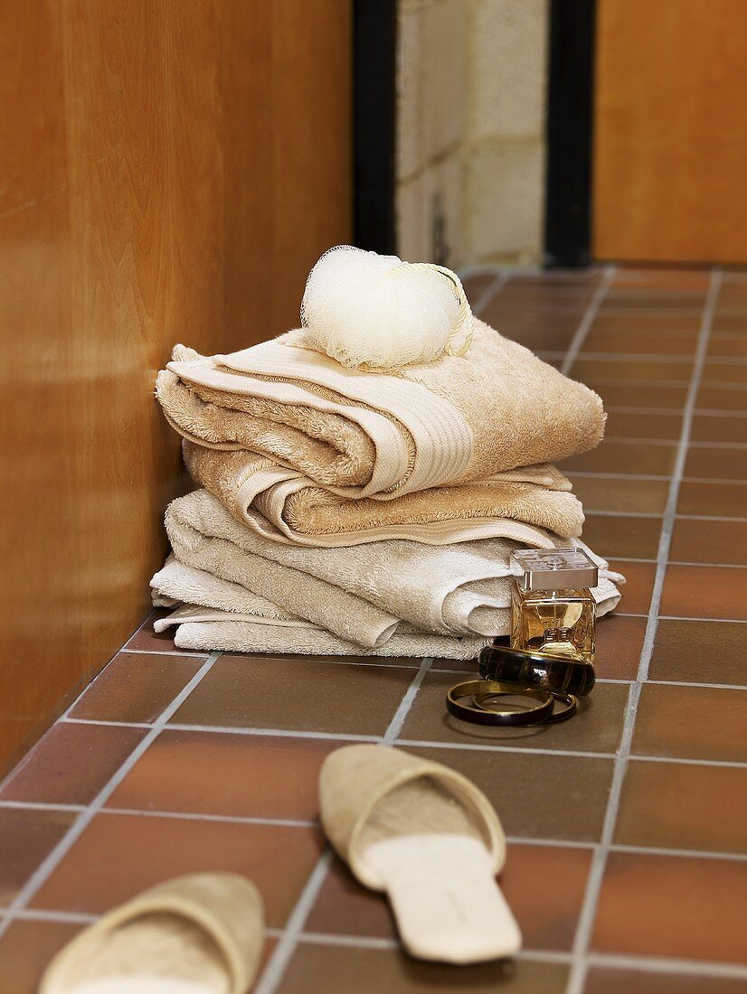 Woman's slippers, perfume, a bracelet and towels on a tiled floor