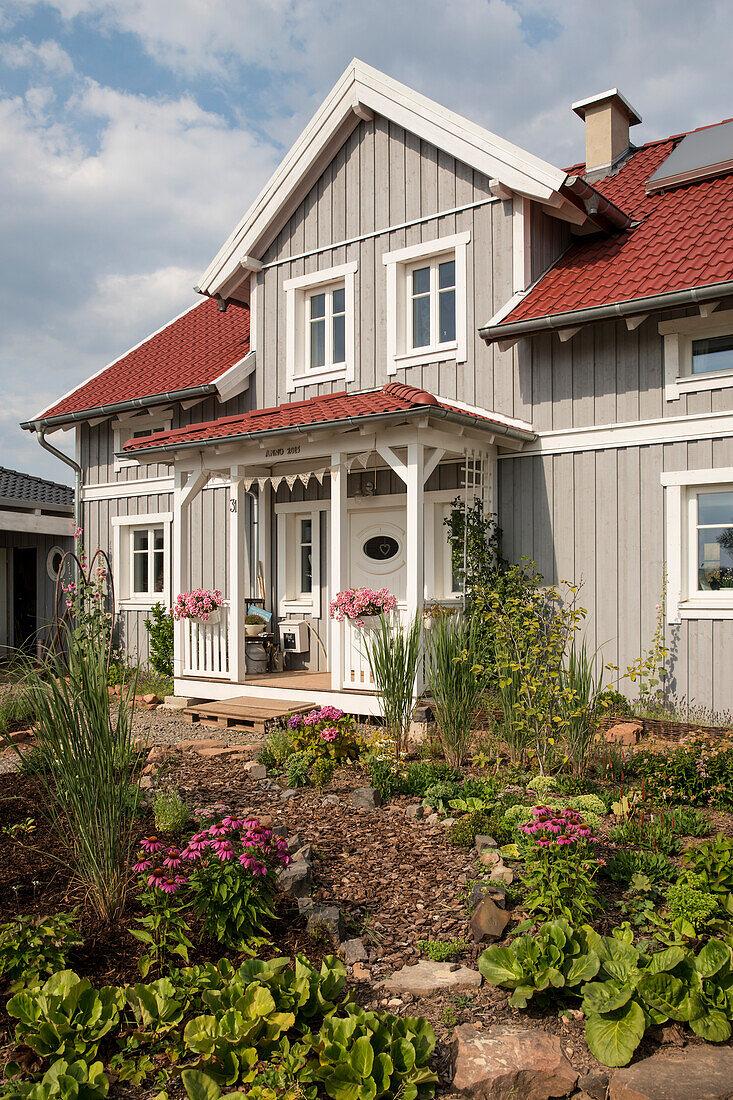 Graues zweistöckiges Einfamilienhaus mit einer Gaube und einem roten Dach im nordischen Stil mit Holzfassade, Korbach, Hessen, Deutschland, Europa
