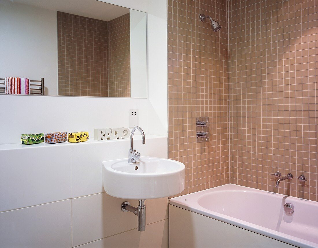 https www living4media com images 00712803 a modern bathroom with light brown wall tiles around a bathtub and a designer wash basin with a mirror