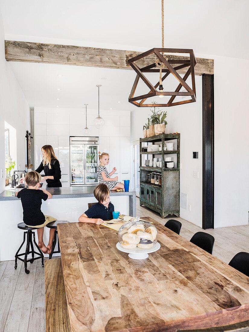 Mutter und Kinder in offener Küche und Essbereich