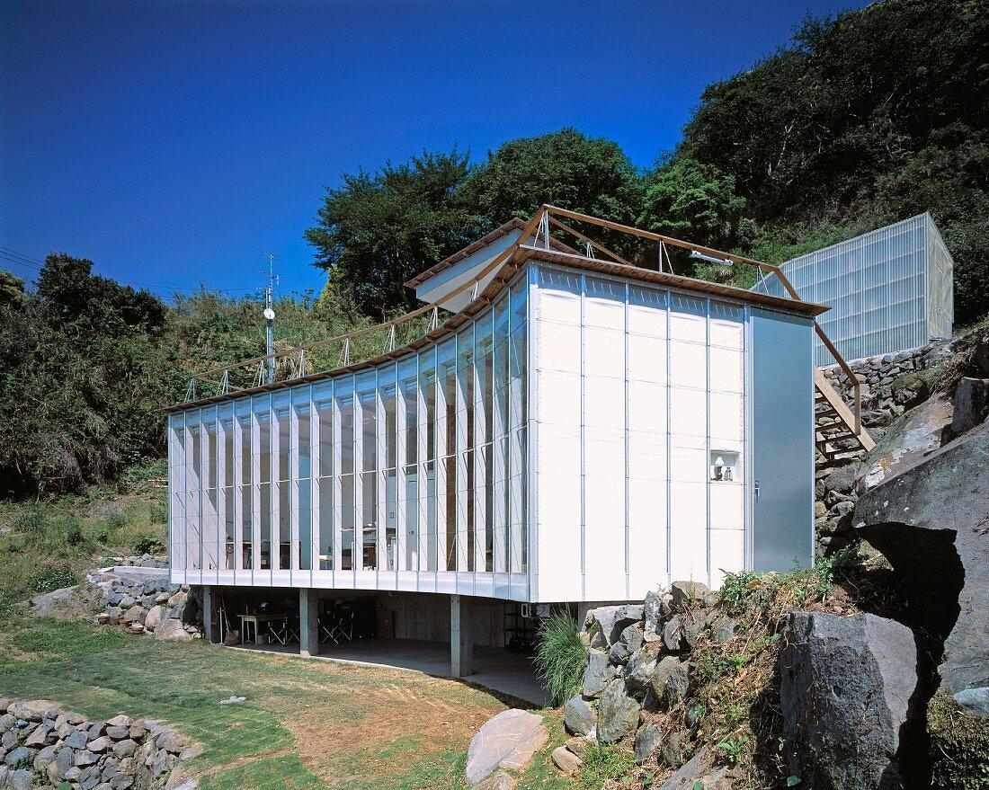Neubauhaus mit geschwungener Fassade am Hang, Haus Izu von Atelier Bow-Wow, Tokio, Japan