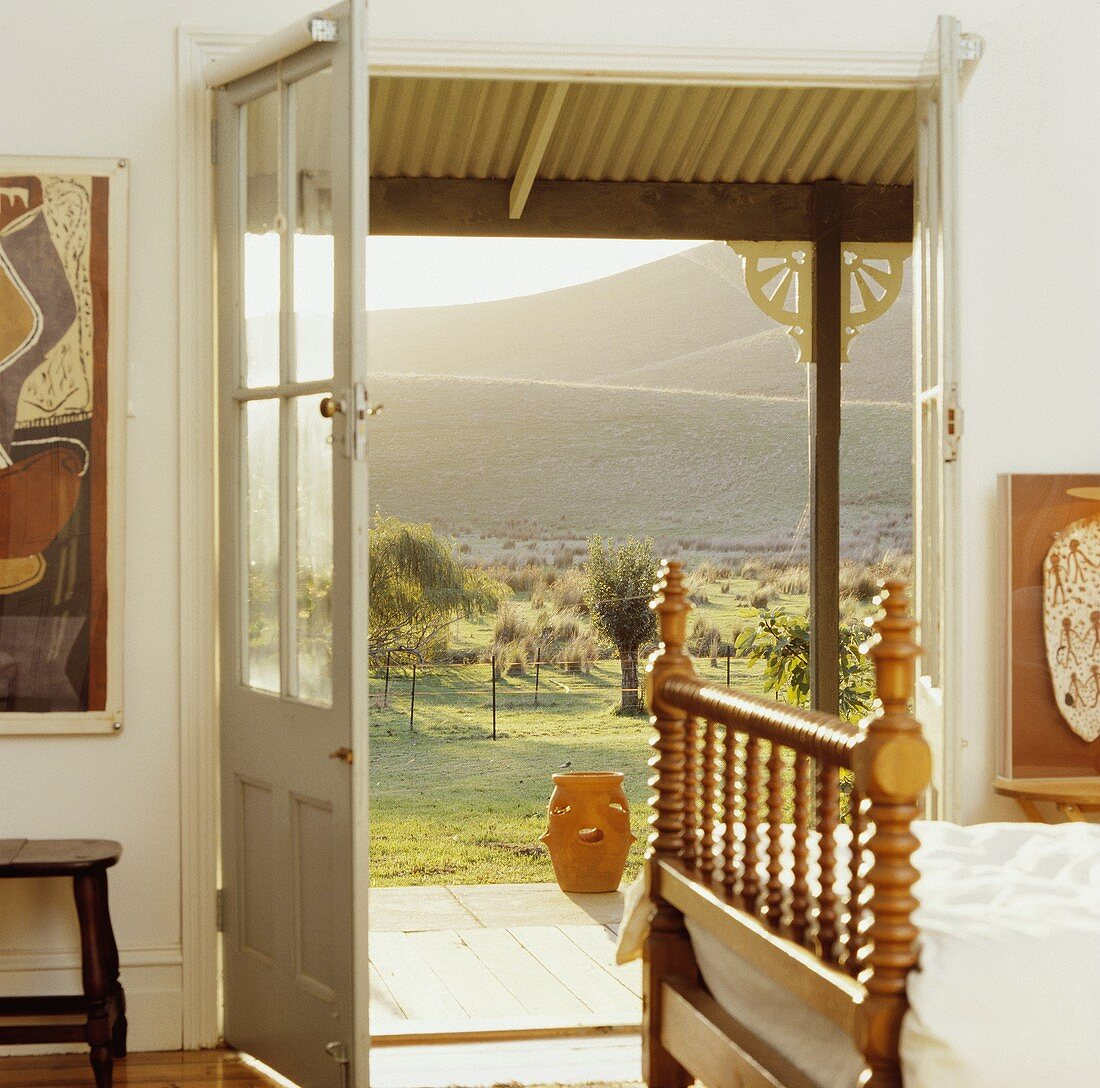 Antikes Holzbett mit gedrechselten Spindeln in weißem, australischem Schlafzimmer mit Blick durch offene Tür in die Landschaft