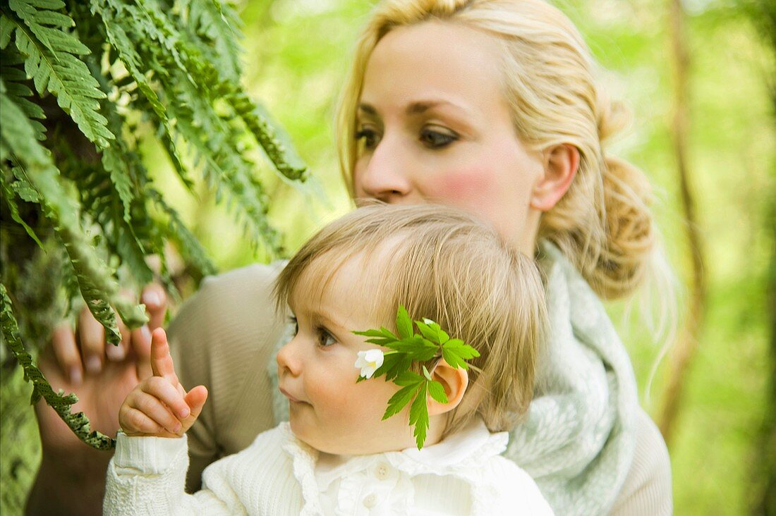 A mother and child looking at ferns in a forest