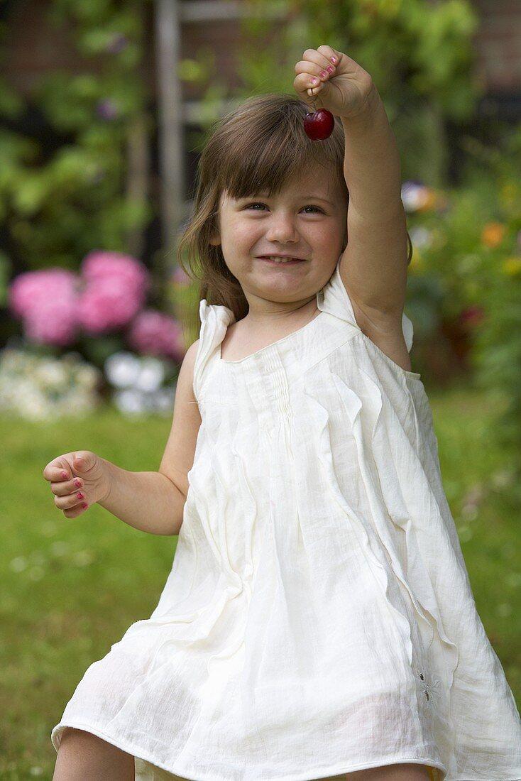 A little girl holding up a cherry