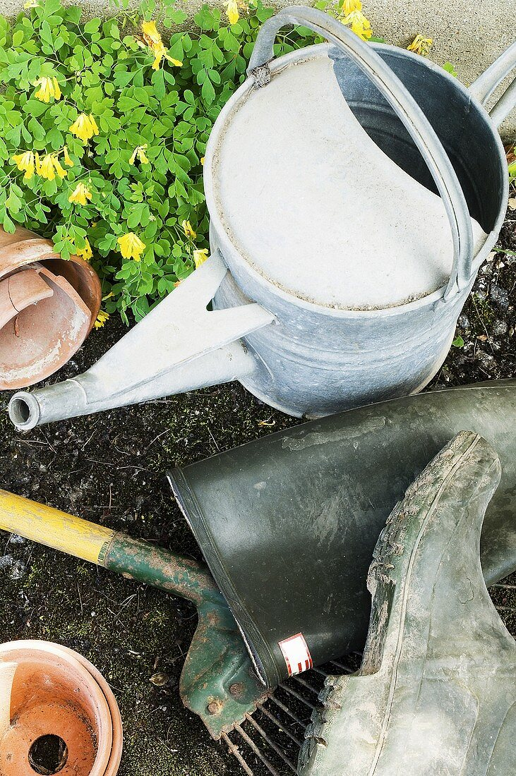 A watering can, wellies and gardening tools