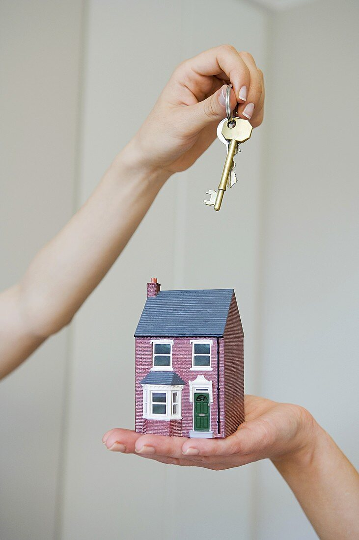 People holding keys and a house