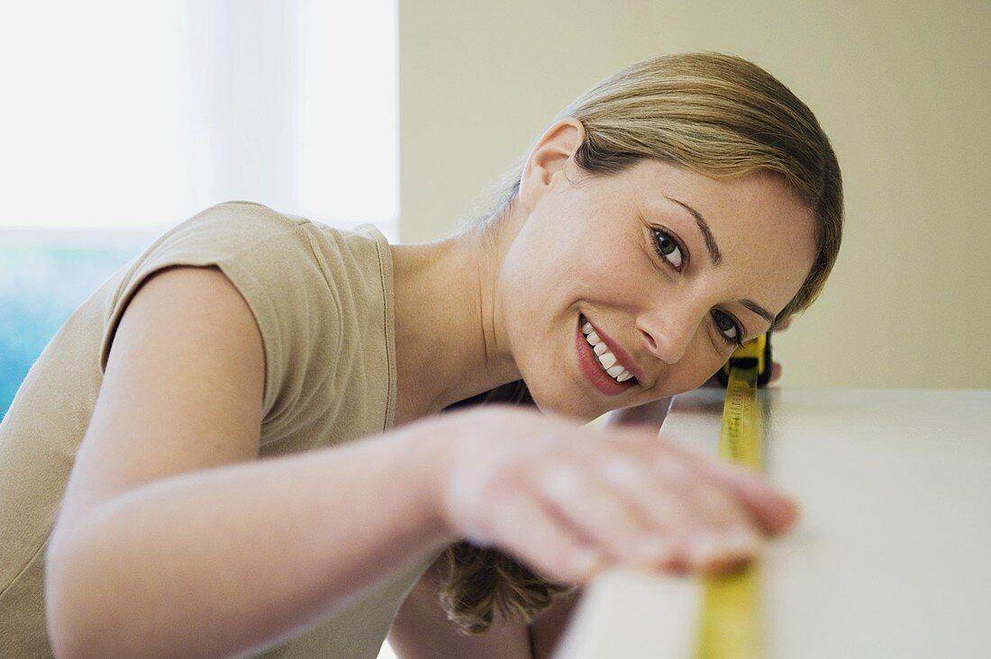 Frau misst ein Regal aus - Bild kaufen - 918959 living4media