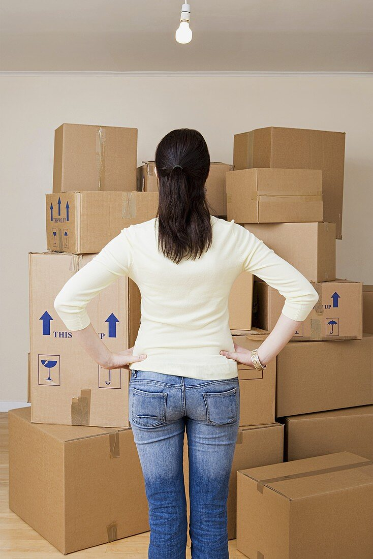 A woman looking at a stack of cardboard boxes