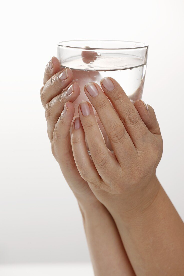 Hands holding a glass of water