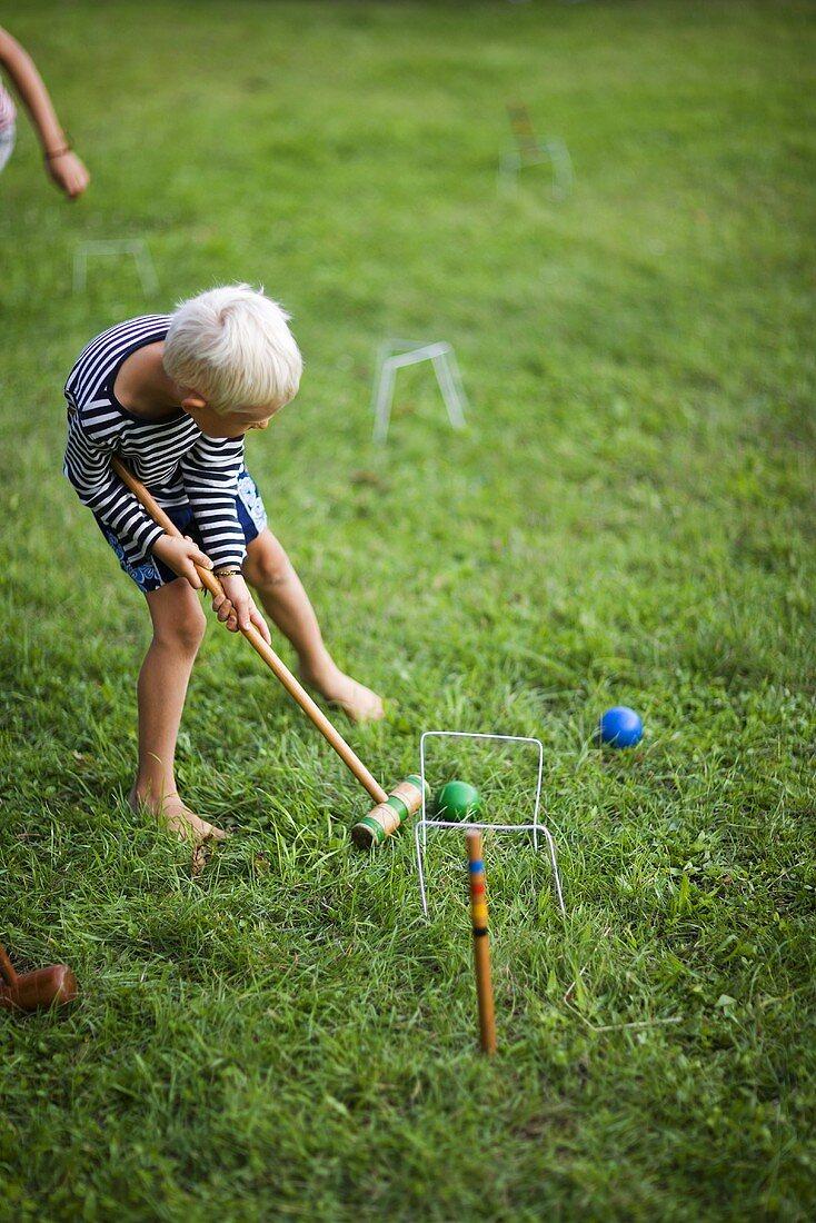 Boy playing croquet