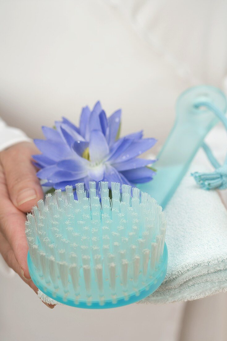 Hands holding brush, water lily and towel