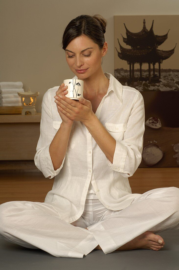 Woman sitting cross-legged with cup of tea