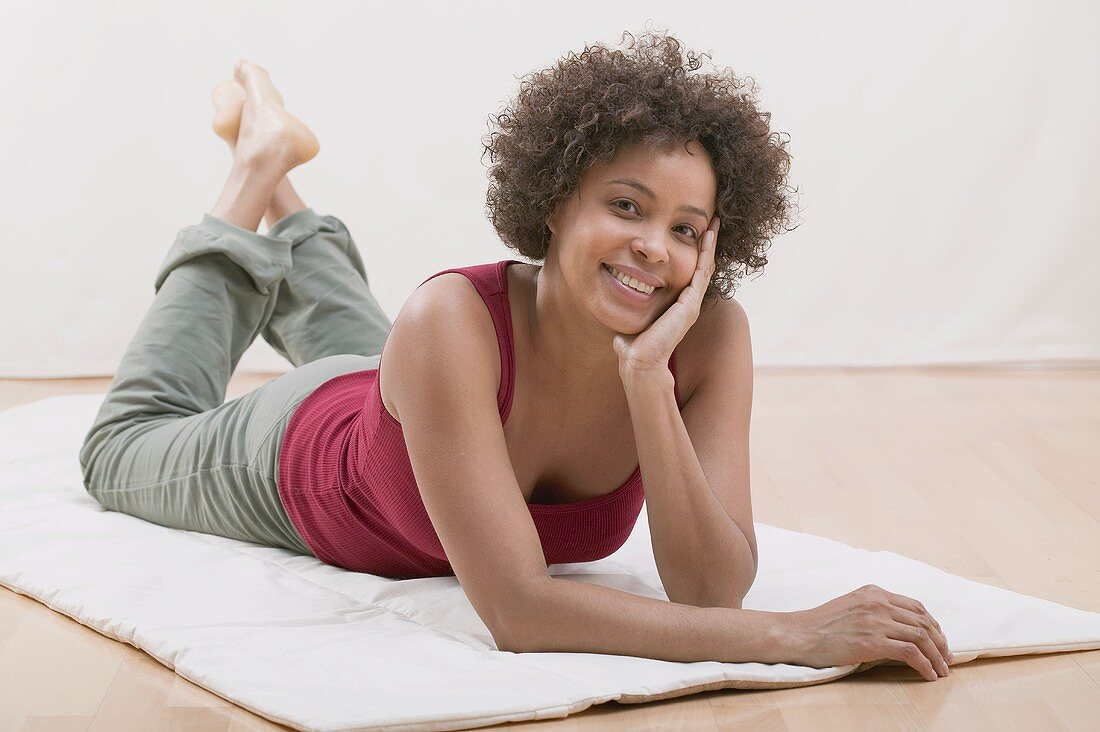 Cheerful young woman lying on a mat (relaxed)