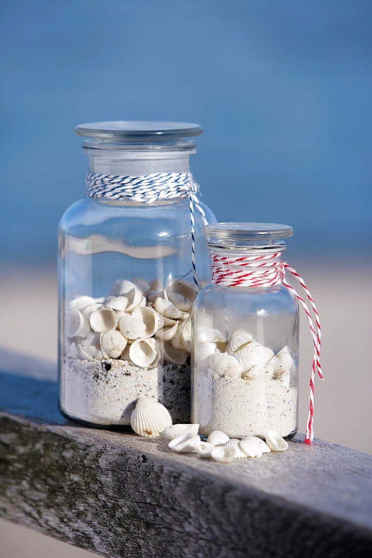 Two storage jars filled with sand and shells