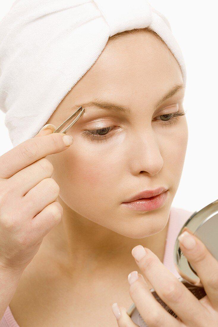 Young woman tweezing her eyebrows, portrait
