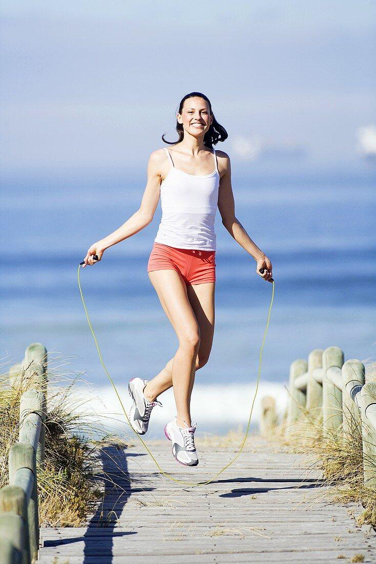 Frau beim Seilspringen am Strand - Bild kaufen - 989675