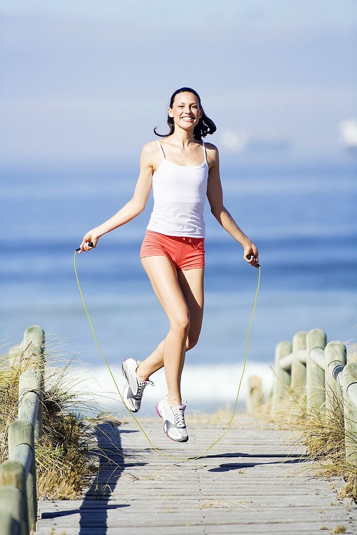 Young woman using skipping rope