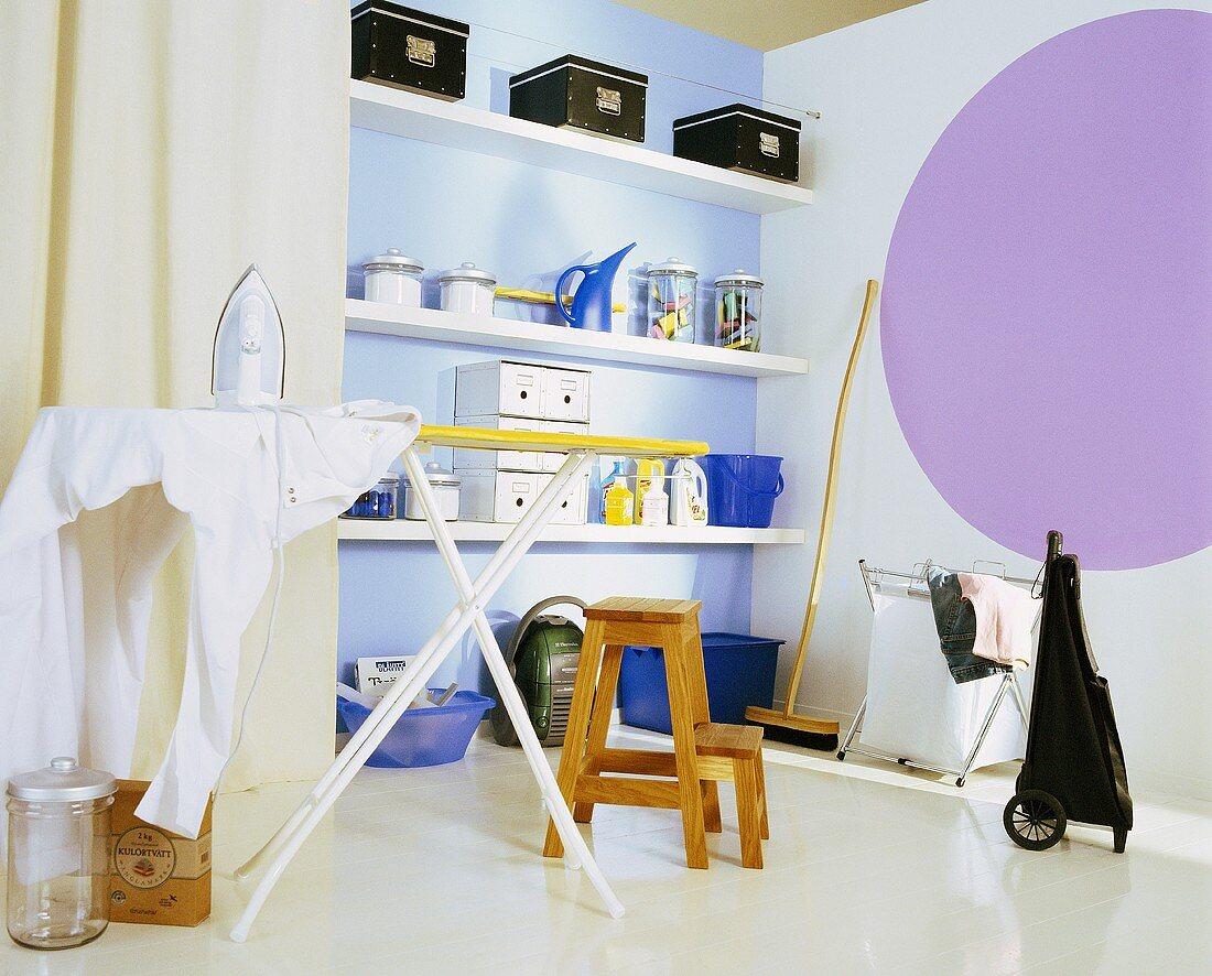 Haushaltsraum mit Wandregal, Bügelbrett, Haushaltsgeräte, Putzutensilien und Vorratskisten