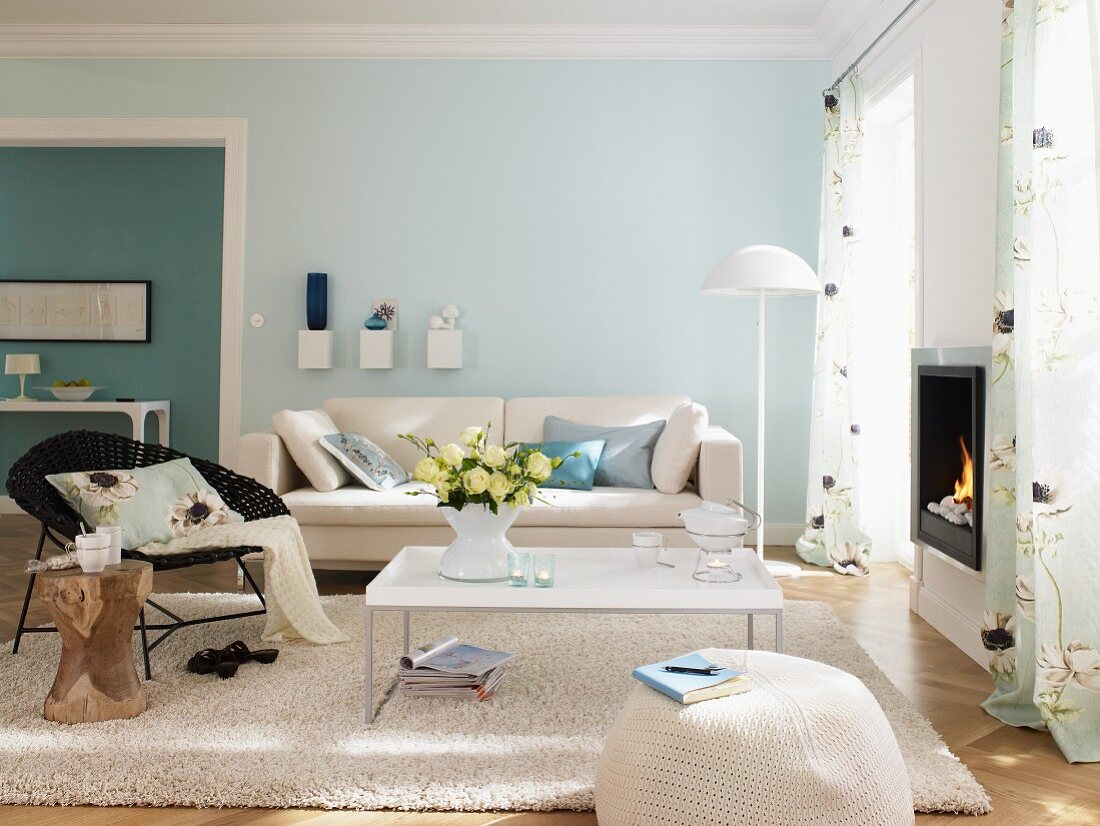 Wohnzimmer mit weissen Möbeln und hellblauer und türkisfarbener Wand