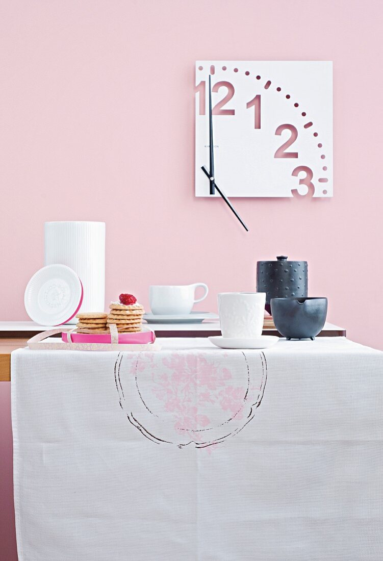 A table laid with tea crockery and cakes against a pink wall with a modern clock