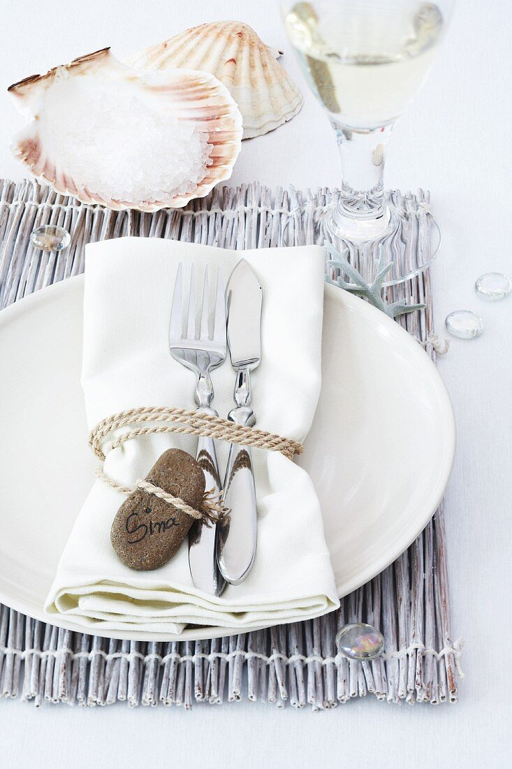 Place setting with name written on pebble and scallop shell as salt cellar