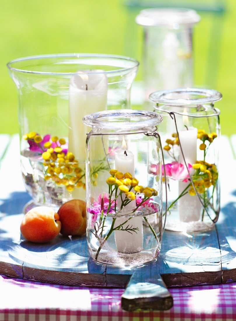 Preserving jars used as candle lanterns and decorated with flowers and water