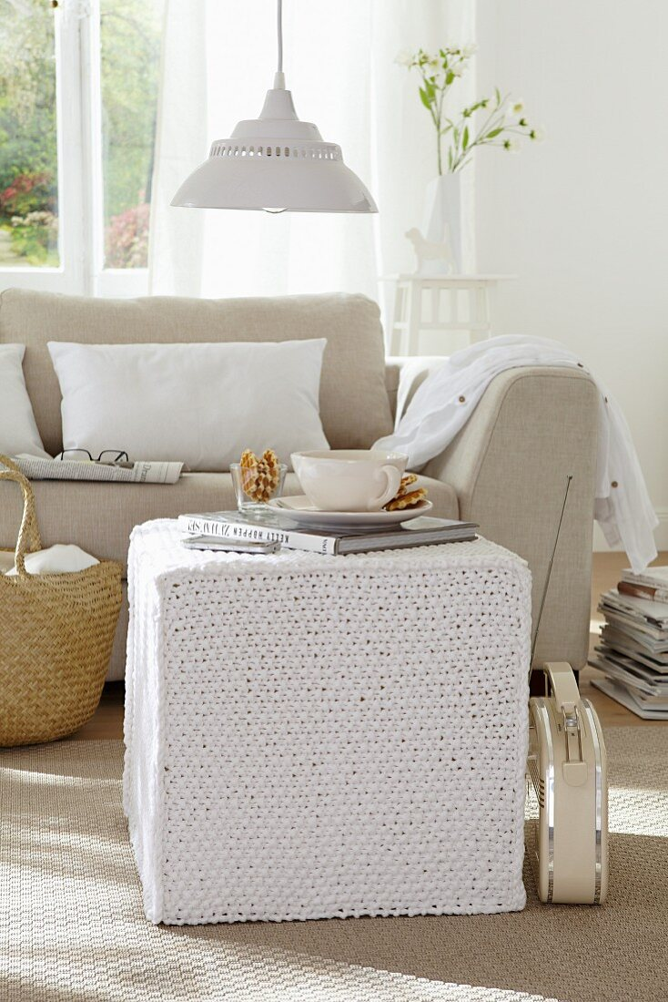 A knitted pouffe in a living room decorated in light tones