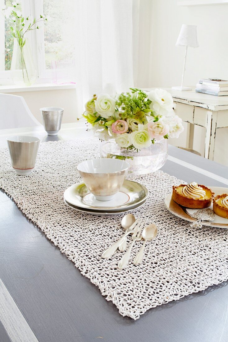 A table laid for coffee with a net-like table runner and bunch of flowers