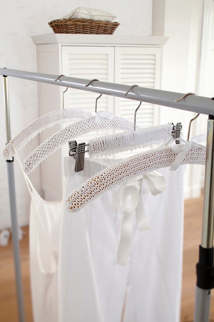 A white knitted cover hanging on a clothes hanger