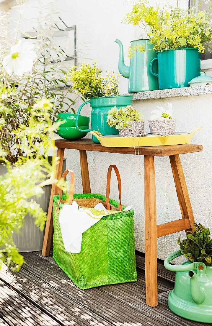 Teak bench, herbs in enamel containers and raffia bag on balcony