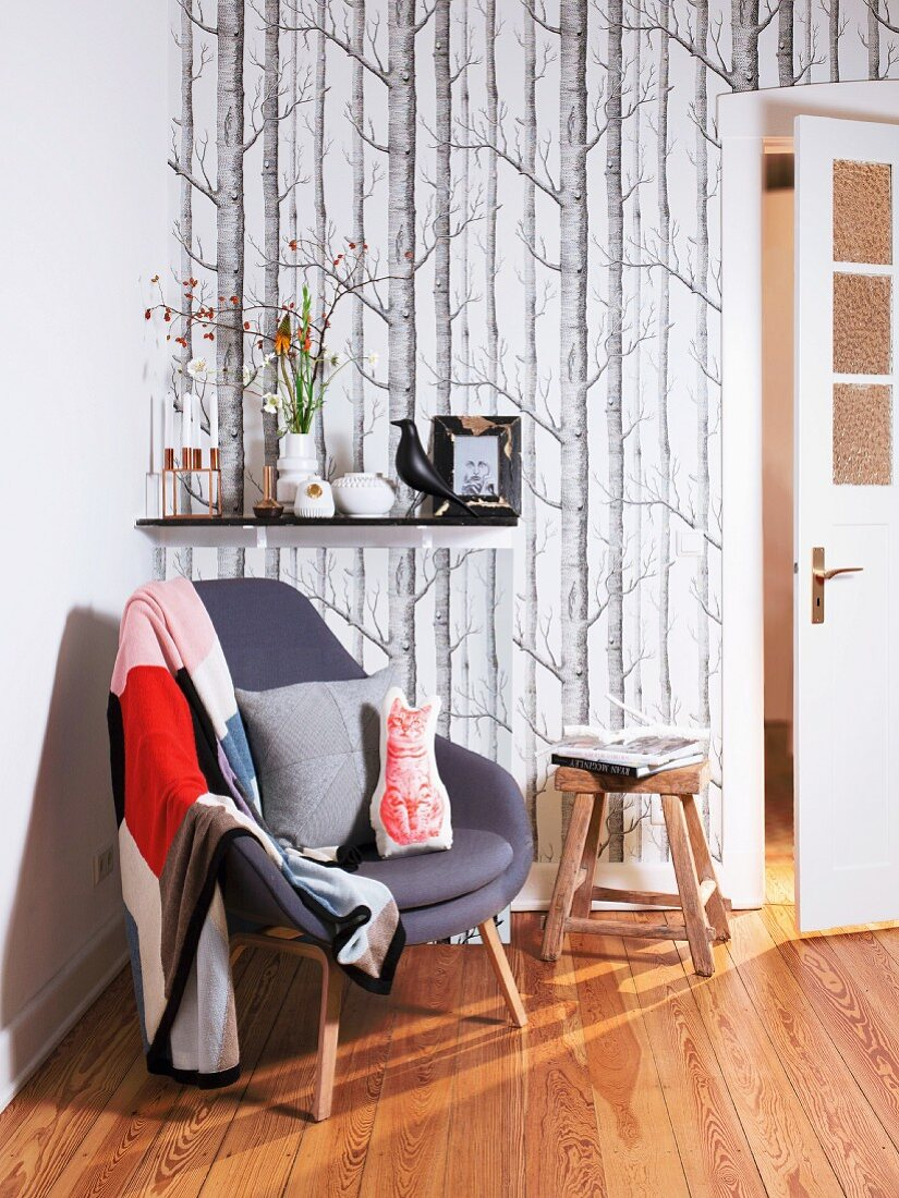 Seating area with armchair & wall bracket on woodland-effect wallpaper
