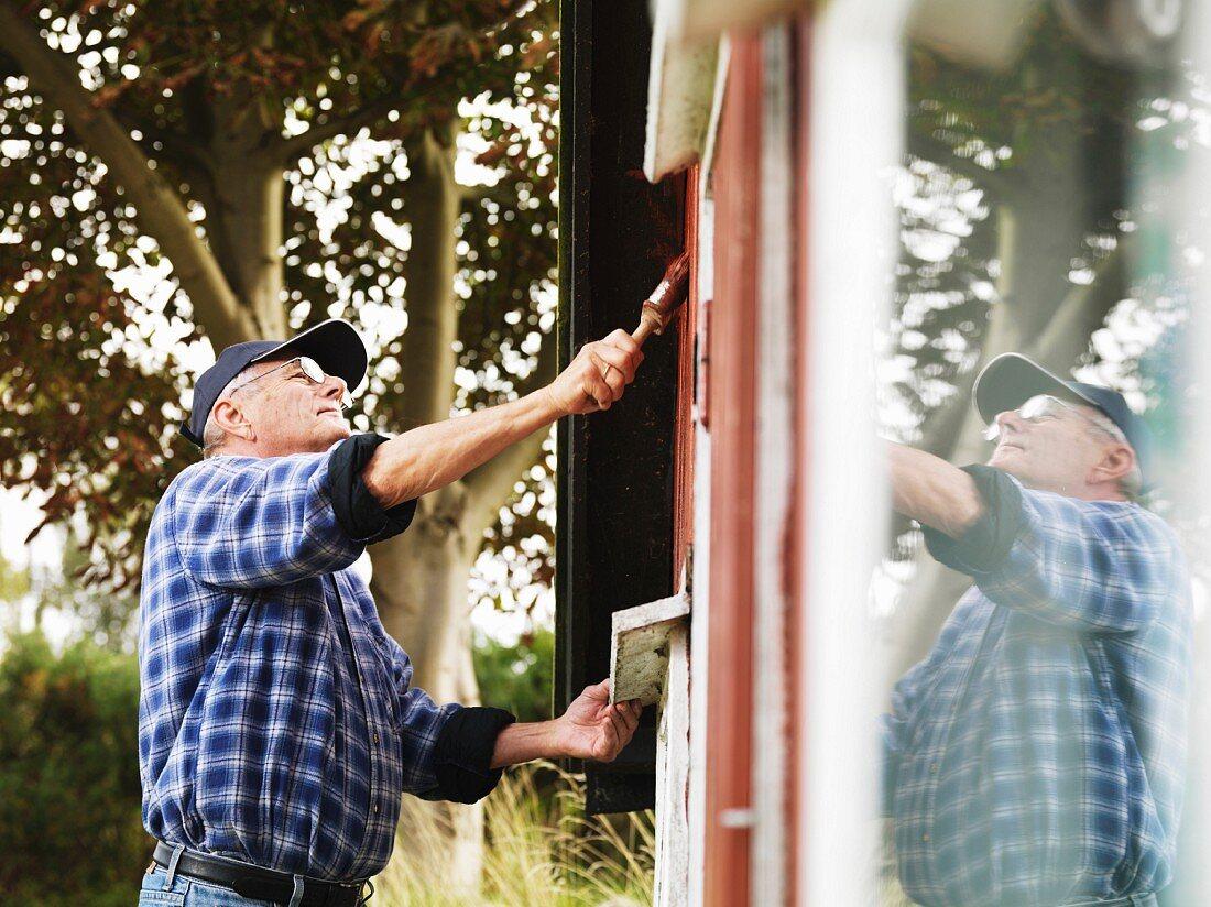 Älterer Mann streicht die Aussenfassade vom Sommerhaus