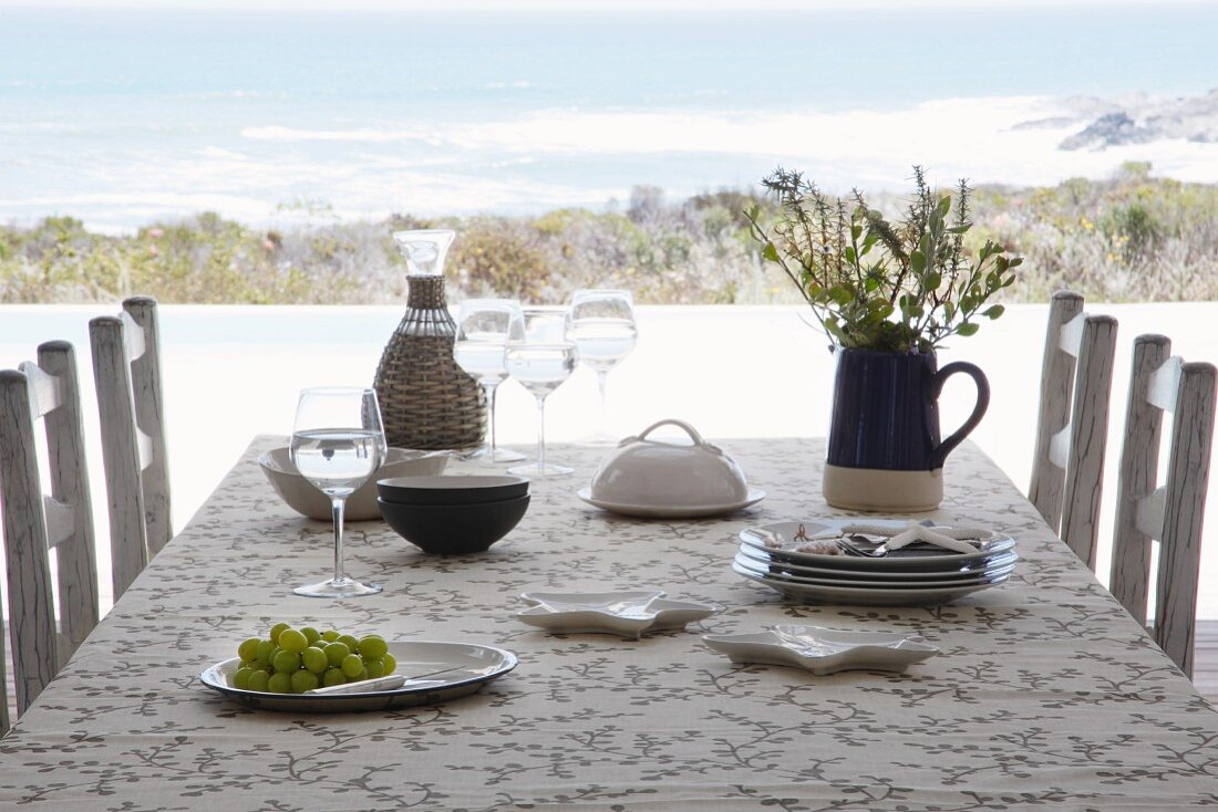 Table set for simple meal with wicker-covered decanter and flowers in jug; view of sea shore in background