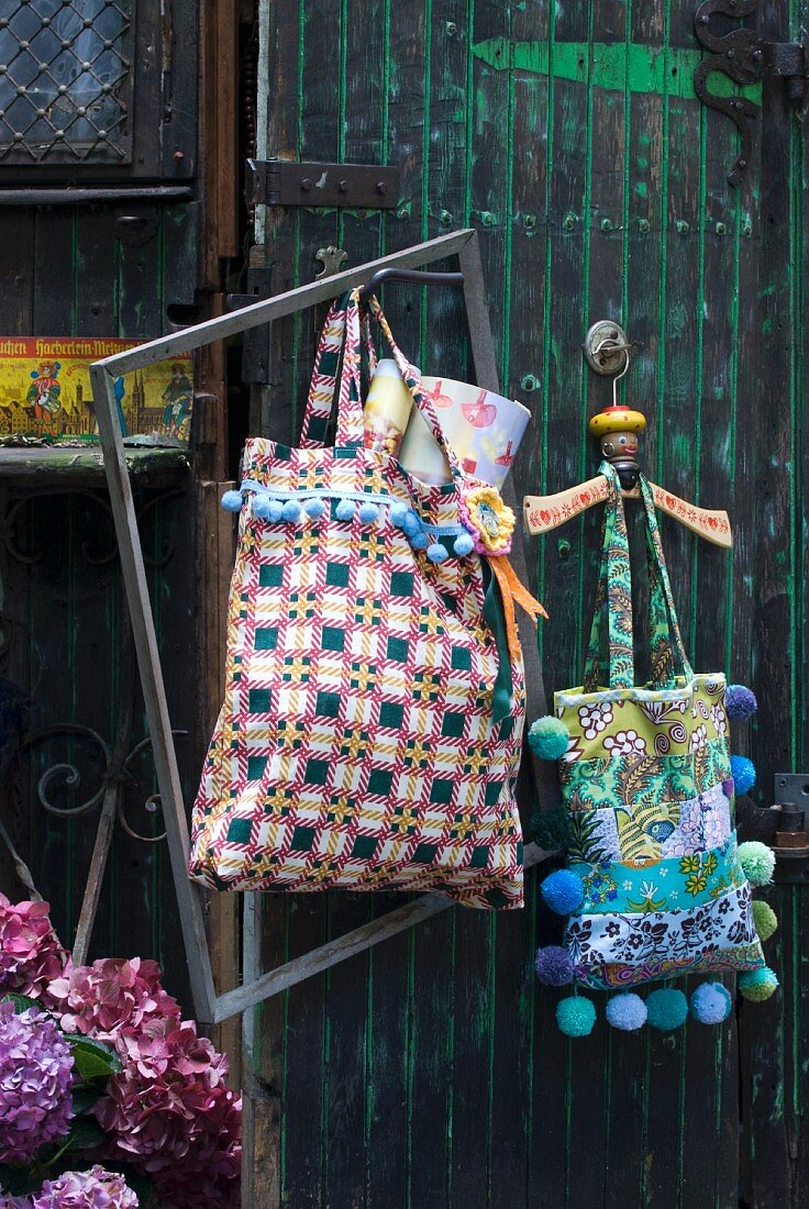 Shopping bags in various patterns decorated with colourful pompoms