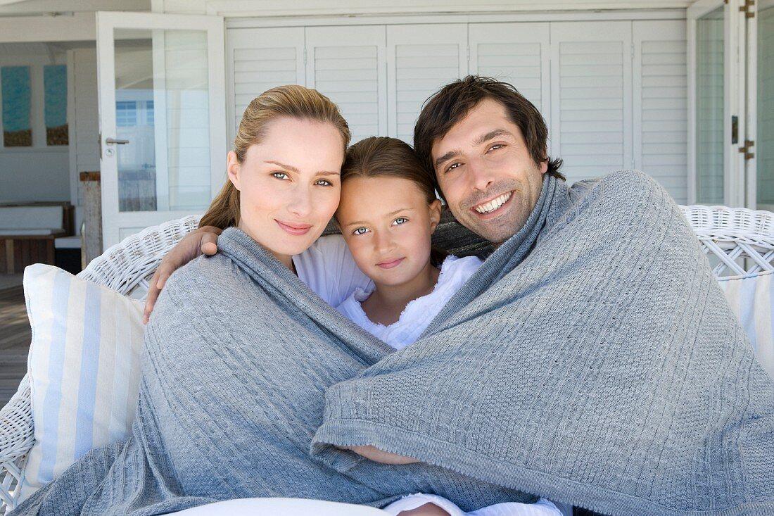 Familie mit einem Kind sitzt mit Decke auf der Terrasse