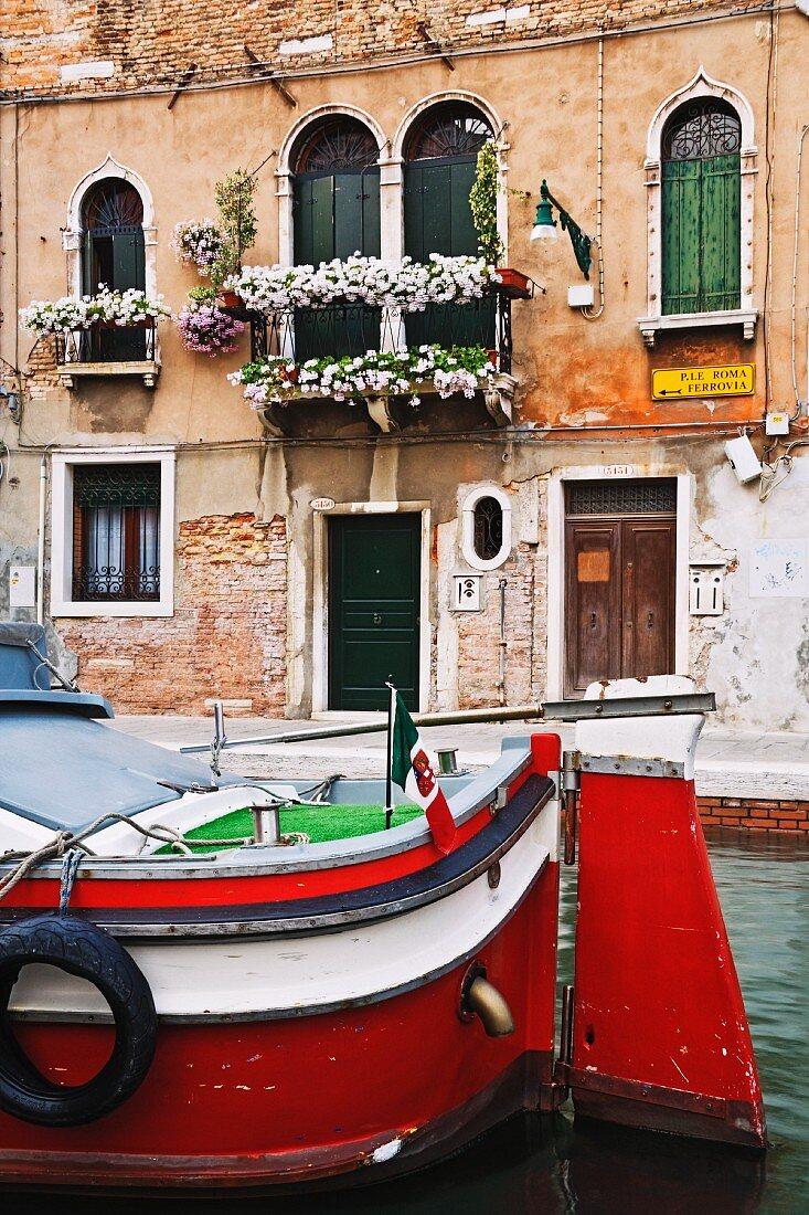 Blumengeschmückter, venezianischer Palazzo; davor ein Motorboot auf dem Wasserlauf