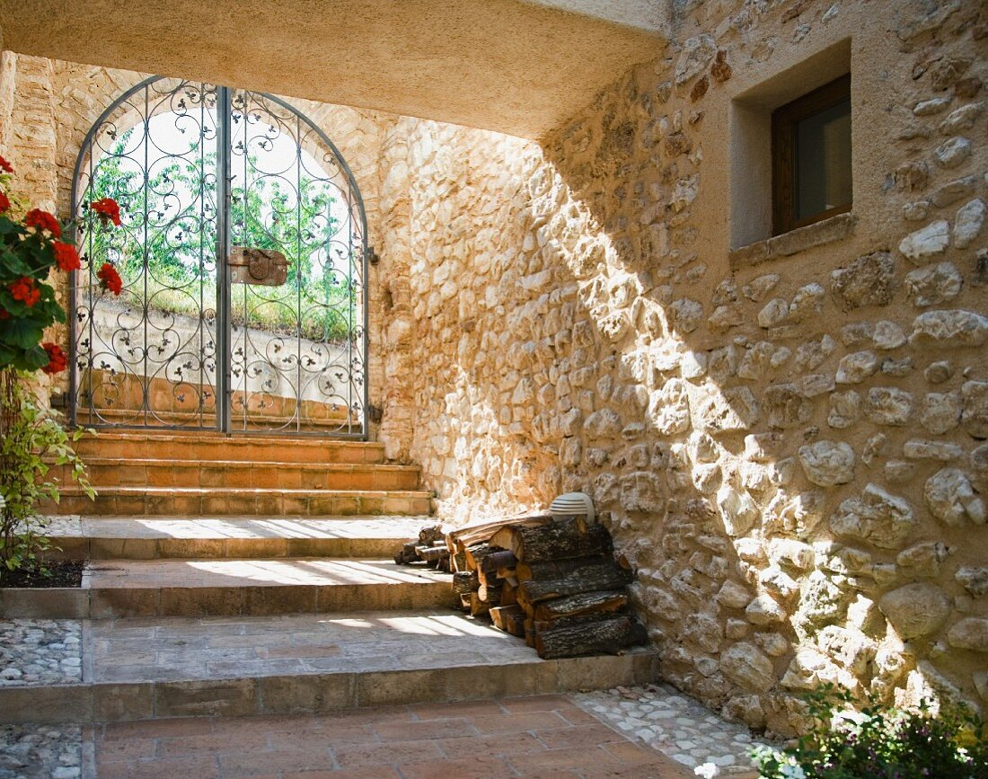 Treppe führt neben Natursteinmauer zum Schmiedeeisernes Tor