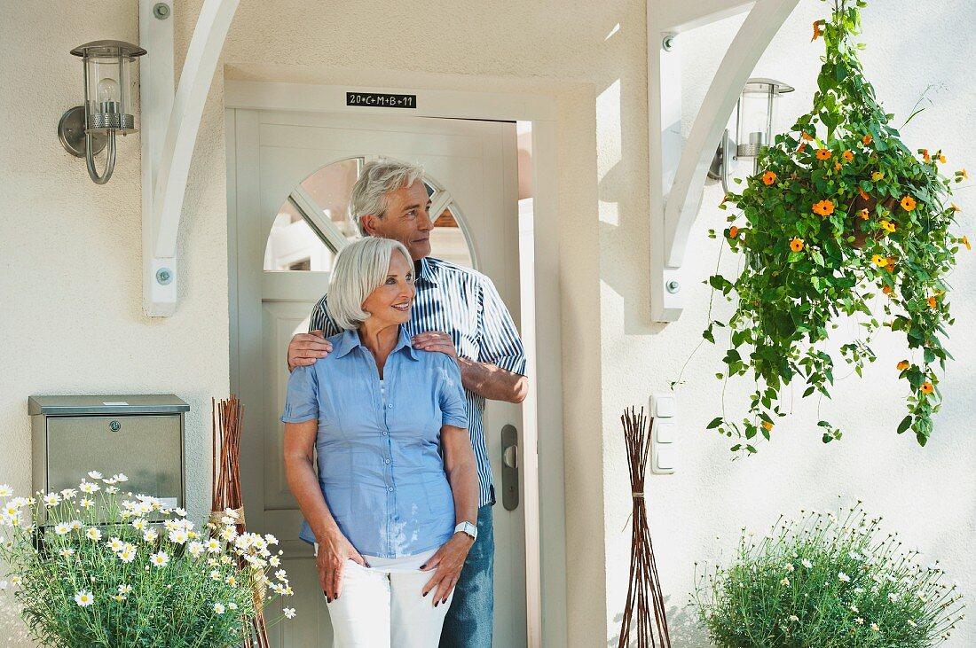 Older couple standing outside front door
