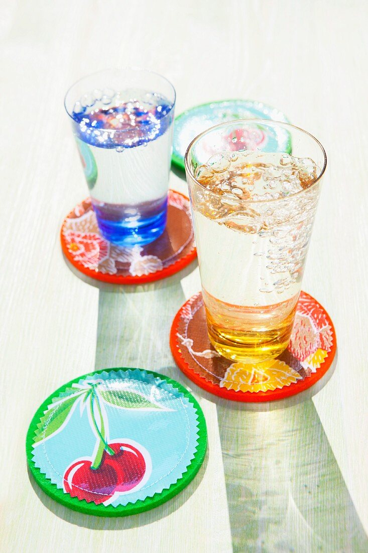Drinking glasses of sparkling water on colourful coasters