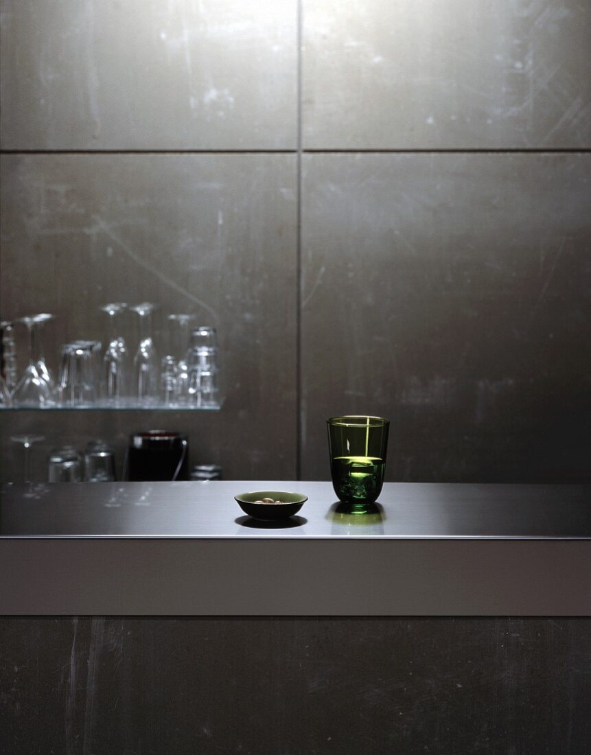 Glasses on stainless steel counter and glass shelf