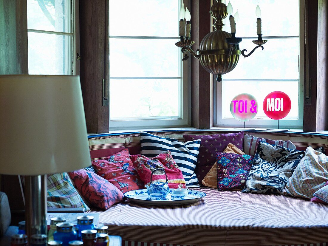 Inviting sofa with many scatter cushions and tea tray in semicircular bay window with illuminated signs reading TOI & MOI